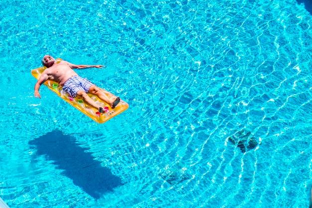 Senior uomo invecchiato dormire e rilassarsi godendosi l'acqua blu della piscina sdraiati sul cocomero rosso lilo