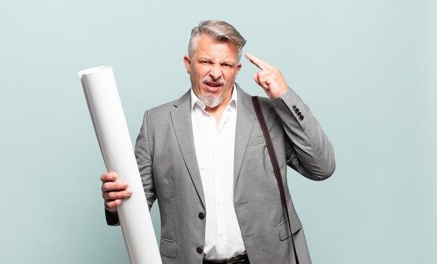 Architetto senior che si sente confuso e perplesso, mostrando che sei pazzo, pazzo o fuori di testa