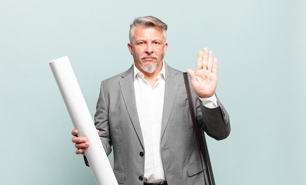Architetto senior dall'aspetto serio, severo, dispiaciuto e arrabbiato che mostra il palmo aperto che fa un gesto di arresto