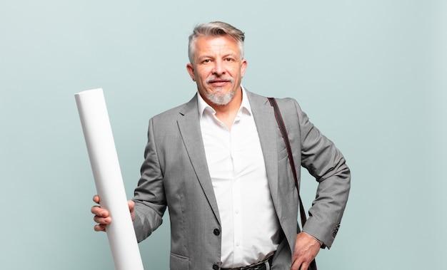 Architetto senior che sorride felicemente con una mano sull'anca e un atteggiamento fiducioso, positivo, orgoglioso e amichevole