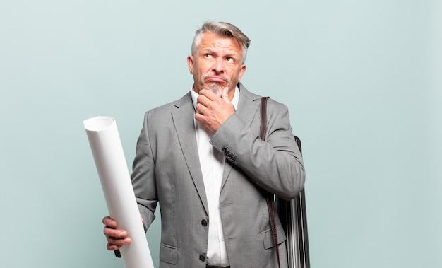 Architetto senior che pensa, si sente dubbioso e confuso, con diverse opzioni, chiedendosi quale decisione prendere