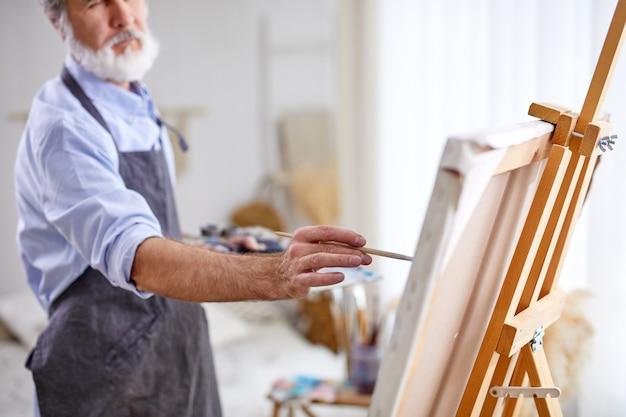 Artista senior che dipinge su cavalletto, tela, pittore professionista intelligente ama l'arte