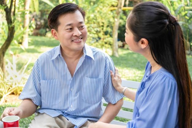 Coppie asiatiche senior che consigliano, rassicuranti e che discutono al parco.