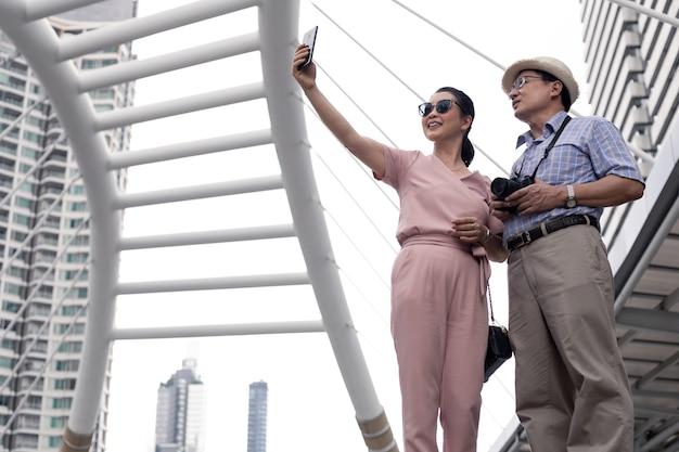 Coppia asiatica anziana in piedi selfie da mobile all'aperto durante il giorno durante un viaggio insieme al punto di riferimento in thailandia. concetto di viaggio di coppia senior.