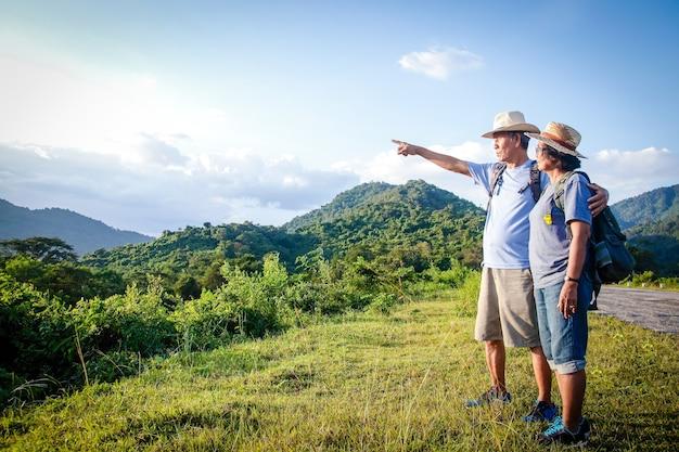 Senior asian couple trekking, viaggiare, vivere una vita felice in pensione sano, può vedere la natura fresca. il concetto di turismo sanitario per gli anziani. con copia spazio.