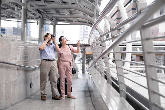 Le coppie asiatiche senior con un uomo smettono di scattare foto e felicemente sorridendo all'aeroporto per prepararsi a viaggiare.