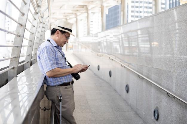 L'uomo asiatico anziano gioca ai telefoni cellulari negli aeroporti per prepararsi a viaggiare all'estero.