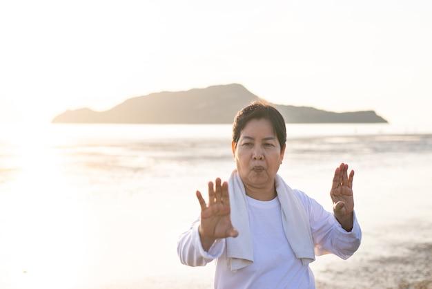 Senior donna asiatica a praticare tai chi esercizio durante il tramonto in spiaggia