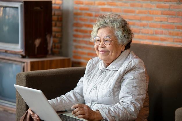 La donna asiatica senior che si siede sul sofà passa il tempo libero a casa usando i social network divertendosi chiacchierando con amici o bambini che godono di una nuova applicazione, il concetto di utente invecchiato avanzato tempo libero.