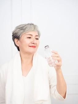 Senior donna asiatica prendendo una pausa durante l'esercizio a casa. donna matura atletica che tiene una bottiglia d'acqua.