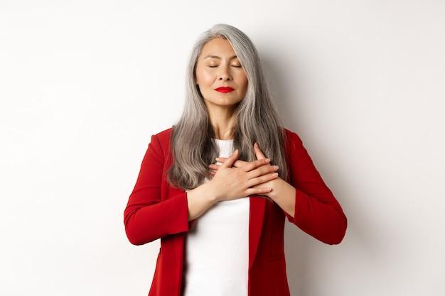 Donna asiatica anziana con labbra rosse e blazer, chiudere gli occhi e tenersi per mano sul cuore grata, sentirsi nostalgica, sognare qualcosa, in piedi su sfondo bianco.