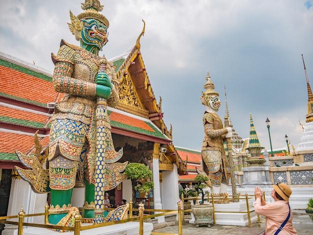 Le donne asiatiche senior fanno una posa tailandese di saluto al gigante nel tempio di wat phrakaew nella città di bangkok tailandia.