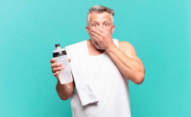Uomo atleta senior che copre la bocca con le mani con un'espressione scioccata e sorpresa, mantenendo un segreto o dicendo oops