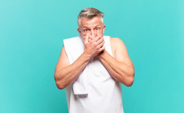 Uomo atleta anziano che copre la bocca con le mani con un'espressione scioccata e sorpresa, mantenendo un segreto o dicendo oops