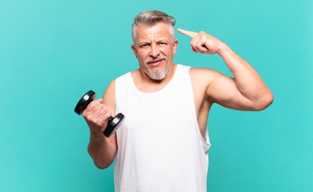 Uomo atleta anziano che si sente confuso e perplesso, mostrando che sei pazzo, pazzo o fuori di testa