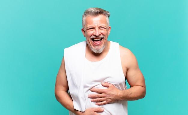 Uomo atleta anziano che ride ad alta voce per qualche scherzo esilarante, sentendosi felice e allegro, divertendosi