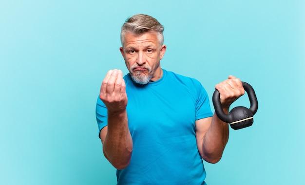 Uomo atleta senior che fa un gesto capice o denaro, dicendoti di pagare i tuoi debiti!