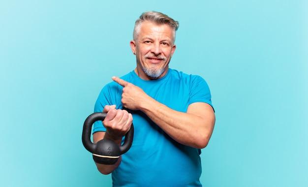 Uomo atleta senior che sorride allegramente, si sente felice e punta di lato e verso l'alto, mostrando l'oggetto nello spazio della copia