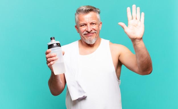 Uomo atleta anziano che sorride allegramente e allegramente, agitando la mano, accogliendoti e salutandoti o salutando