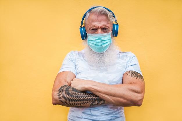 Uomo anziano dell'atleta che indossa una maschera medica per la prevenzione del coronavirus mentre ascolta la musica della playlist