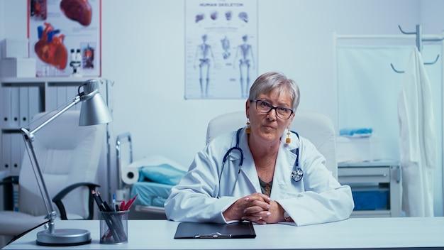 Personale medico senior autentico che offre consulenza online durante la pandemia glabale covid-19. concetto di sistema sanitario remoto. lavorare nel settore sanitario utilizzando la tecnologia moderna. medicina sanitaria