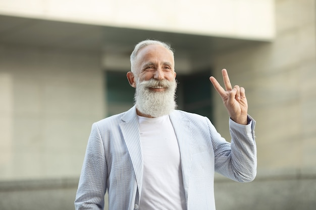 Uomo maggiore della barba che mostra il segno di pace