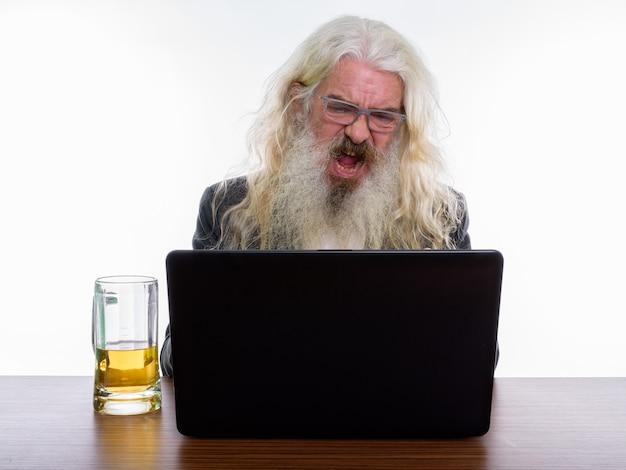 Anziano, barbuto, uomo affari, bere, vetro birra, mentre, usando, laptop