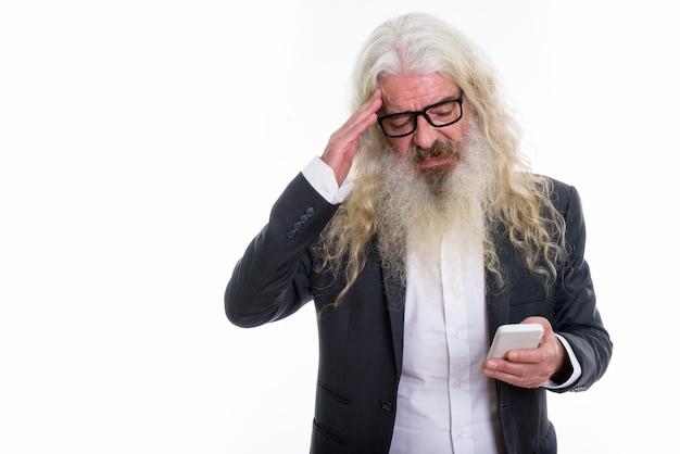 Uomo d'affari barbuto anziano che ha mal di testa