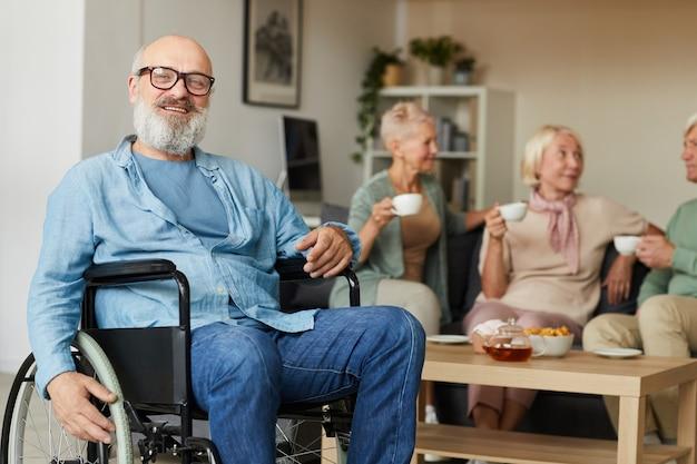 Senior barbuto disabile seduto in sedia a rotelle e sorride alla macchina fotografica alla casa di cura