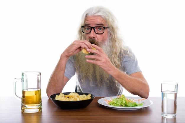 Uomo barbuto anziano che mangia patatine fritte con healt