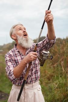 Uomo barbuto anziano che pesca su un lago