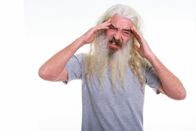 Uomo barbuto anziano che ha mal di testa con entrambe le mani in testa