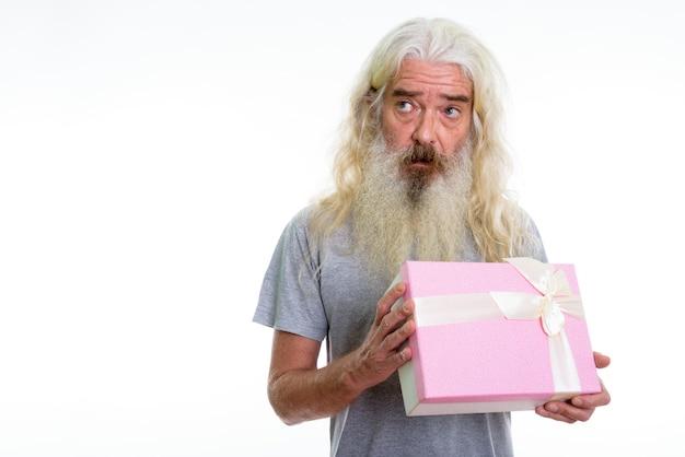 Anziano uomo barbuto azienda confezione regalo mentre si pensa