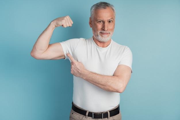 Senior uomo barbuto che mostra i muscoli che indossano maglietta bianca in posa. l'uomo serio indica i suoi bicipiti perfetti