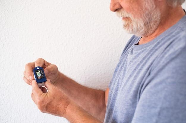 L'uomo anziano con la barba mostra come misurare il livello di saturazione di ossigeno nel sangue con il dispositivo ossimetro digitale