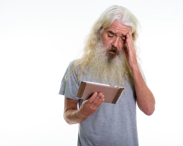 Uomo barbuto anziano utilizzando tavoletta digitale