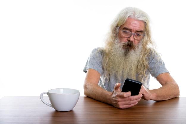 Uomo barbuto anziano utilizzando il telefono cellulare con il caffè