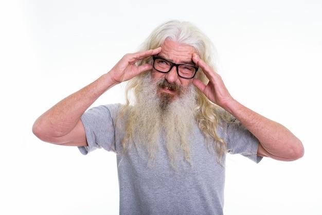 Anziano uomo barbuto che indossa occhiali da vista pur avendo mal di testa