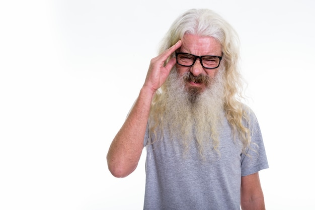 Uomo barbuto anziano che indossa occhiali da vista mentre havinng mal di testa
