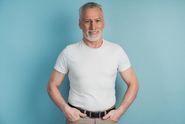 Uomo anziano e barbuto in una posa bianca della maglietta