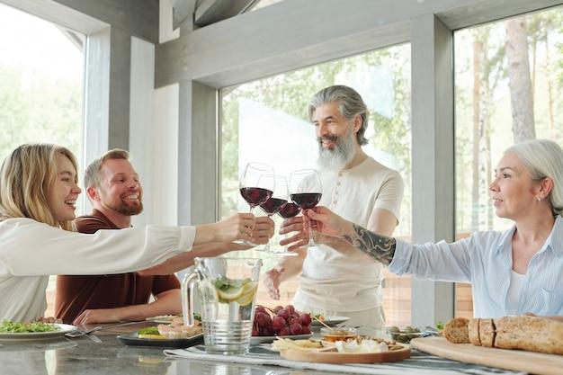 Uomo barbuto anziano con un bicchiere di vino rosso che beve pane tostato con i membri della famiglia durante la cena