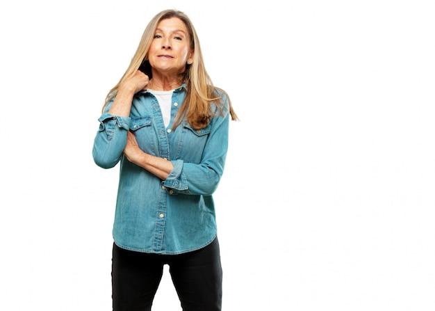 Senior bella donna con un gesto stressato, sudando e tirando il collo della camicia aperto, sentendosi soffocato