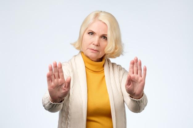 Senior donna bionda che indossa abiti gialli e bianchi che mostra il segnale di stop