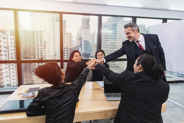 L'uomo d'affari senior dà il cinque con il collega asiatico nella sala riunioni in ufficio dopo la presentazione del termine per le nuove attività
