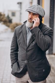 Uomo d'affari anziano che usa il telefono in strada