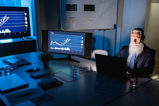 Uomo d'affari senior che lavora di notte all'interno dell'ufficio della società fintech