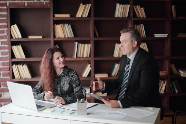 Imprenditore senior e assistente che lavora in un ufficio moderno.