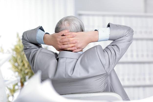 Uomo d'affari senior che sogna di sedersi alla sua scrivania in ufficio