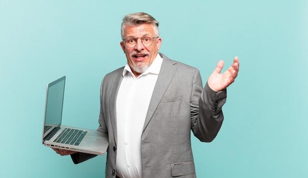 Uomo d'affari senior che si sente felice, sorpreso e allegro, sorride con atteggiamento positivo, realizza una soluzione o un'idea