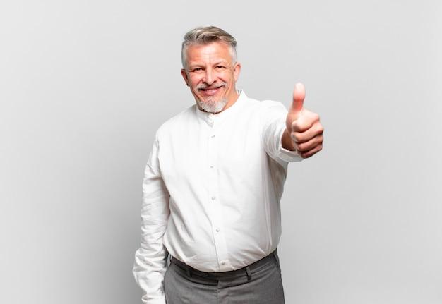Uomo d'affari anziano che si sente orgoglioso, spensierato, fiducioso e felice, sorride positivamente con il pollice in alto